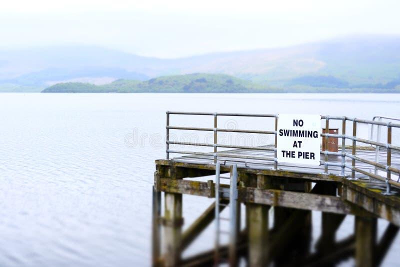 Nenhuma natação no perigo do sinal de aviso de Loch Lomond Luss das águas profundas do molhe do cais da morte fotografia de stock