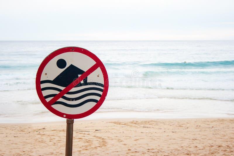 Nenhuma natação permitiu o sinal na praia com a onda forte do mar pelo fundo da praia imagem de stock