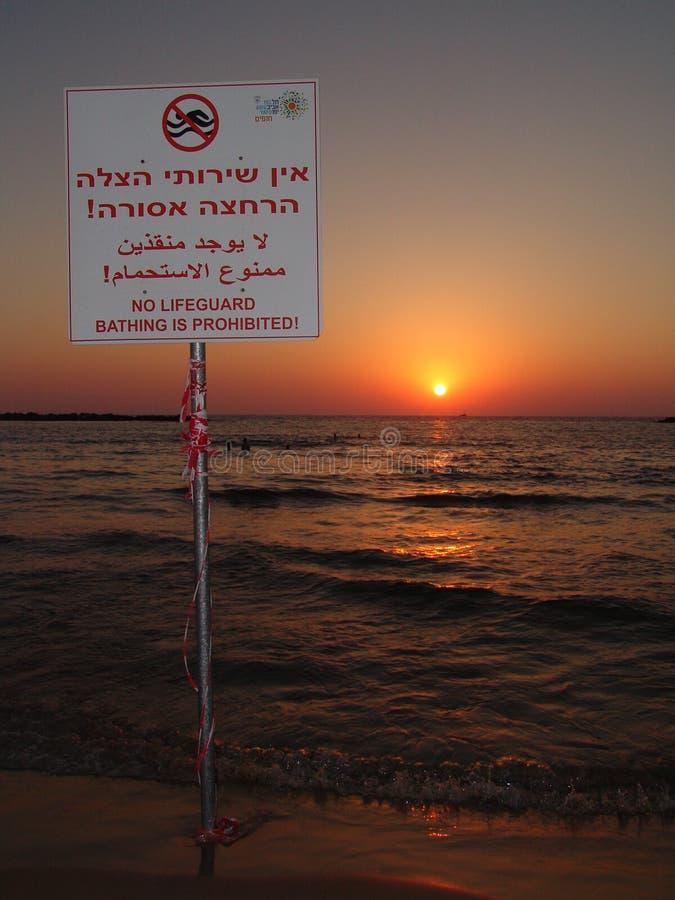 Nenhuma salva-vidas, sinal proibido nadador em uma praia de Tel Aviv em morno, por do sol do verão imagens de stock royalty free