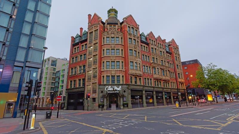 Neo-klassisk byggnad med shoppar i gatorna av Manchester arkivbild