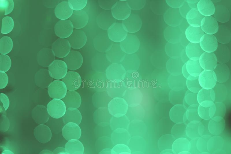 Neo-mint bokeh of garland lights texture. abstract blurred background in trendy 2020 neo mint tones royalty free stock photos