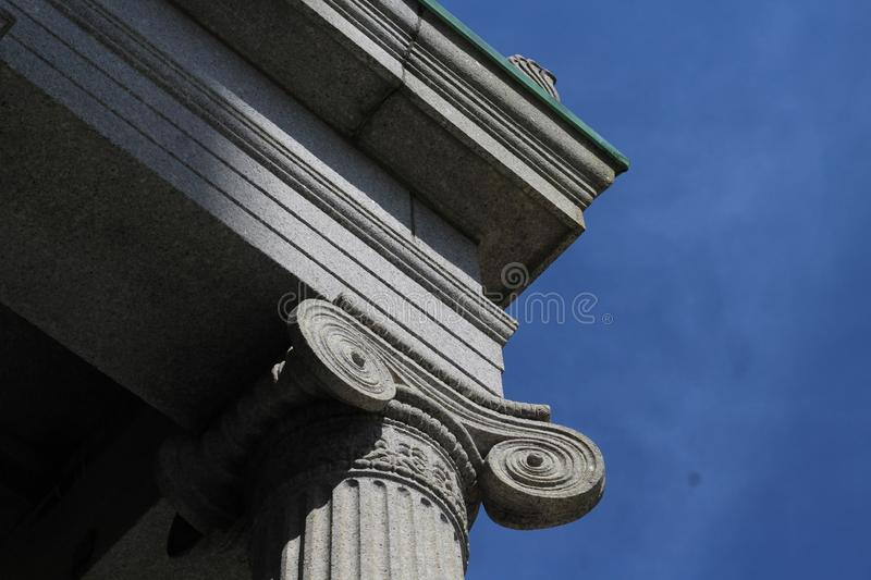Neoclassical lonic style column with blue sky in the background royalty free stock photo