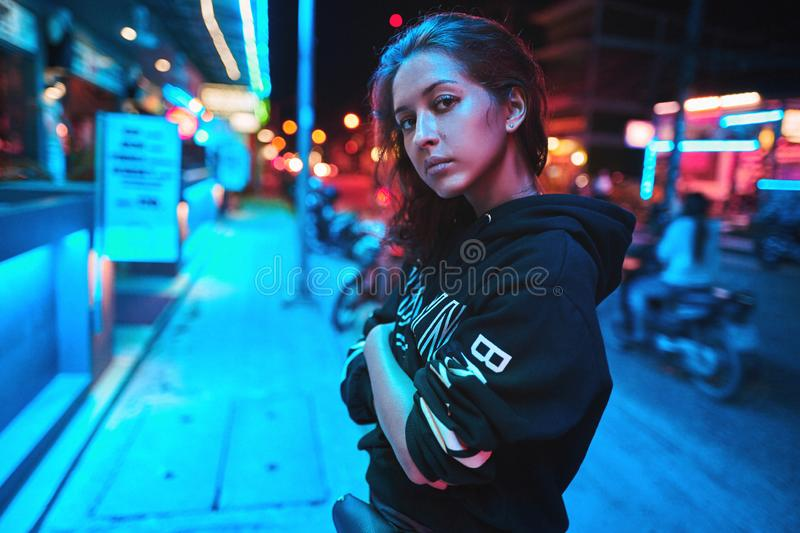 Neon close up portrait of young woman wear hoodie. night city street shot. Neon close up portrait of young beautiful woman wear hoodie. night city street shot royalty free stock images