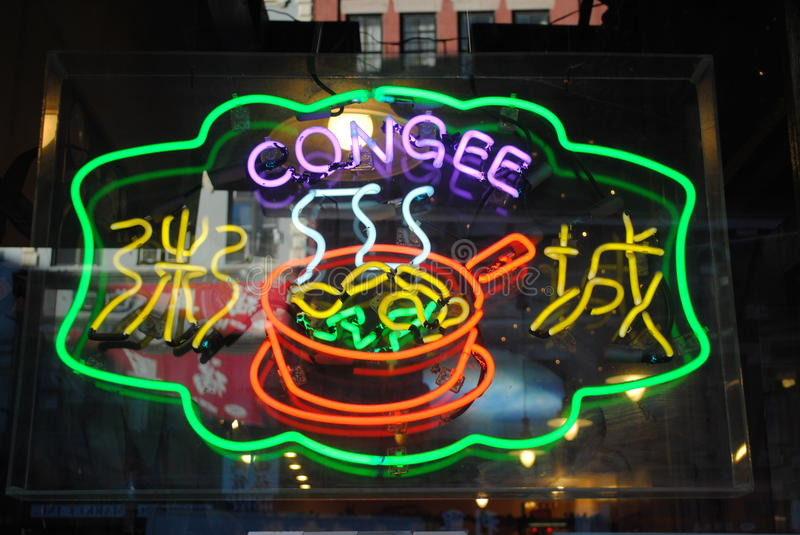 Neon Congee Sign, New York City Chinatown at Night. A neon sign in the window of a chinese restaurant advertises congee rice porridge royalty free stock images