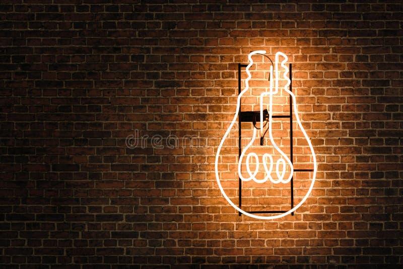 Neon della lampadina sul muro di mattoni vuoto immagini stock libere da diritti