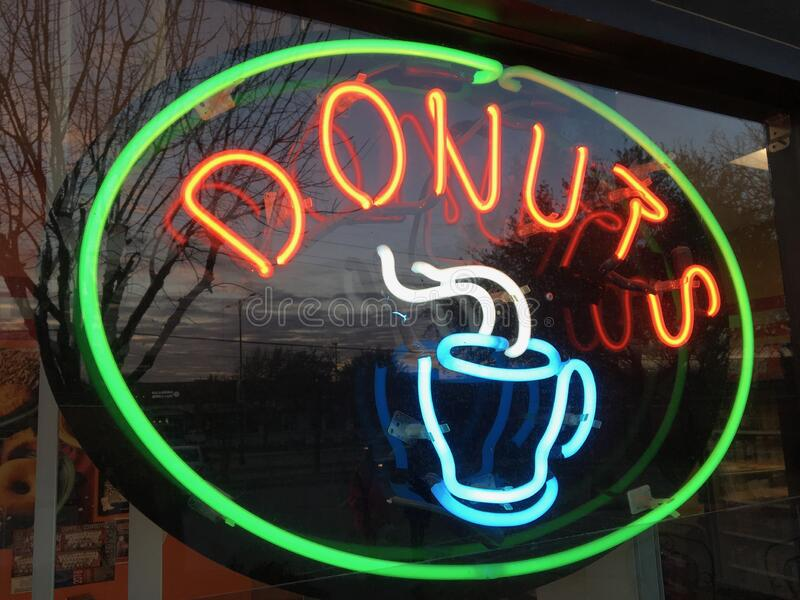 Neon Donuts and Coffee Sign in a Window royalty free stock images