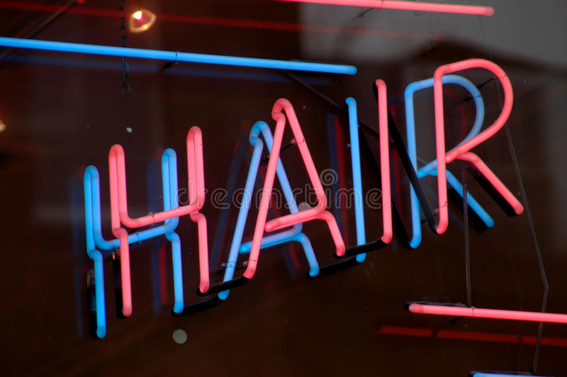 Neon hair sign. A neon sign in the window or a hair salon stock image
