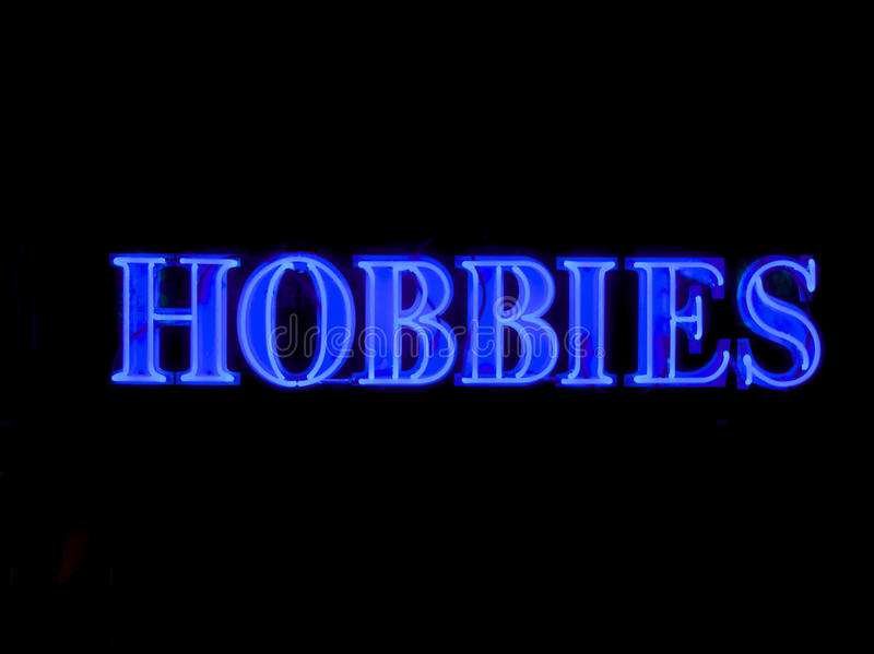 Neon hobbies sign. The word hobbies witten in blue neon royalty free stock images