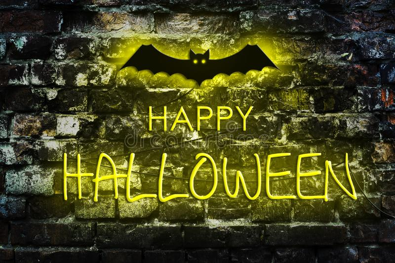 Neon inscription Happy Halloween on the background of an old brick wall. Holidays royalty free stock photography