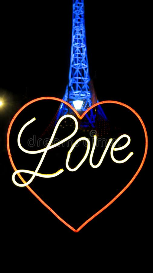 Neon lights of word Love with heart symbol and the Melbourne Arts Centre Spire illuminated in blue. At white night festival in Mlebourne, Australia royalty free stock photo