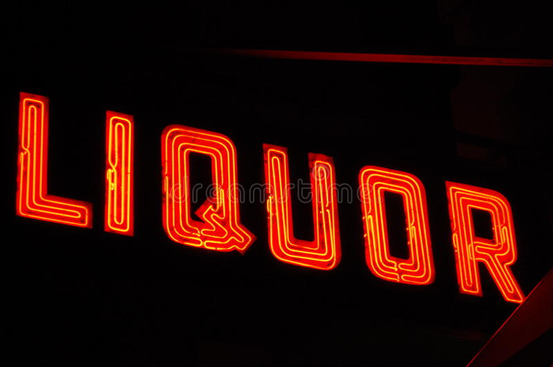 Neon Liquor Sign. A red neon sign advertises liquor for sale royalty free stock photography