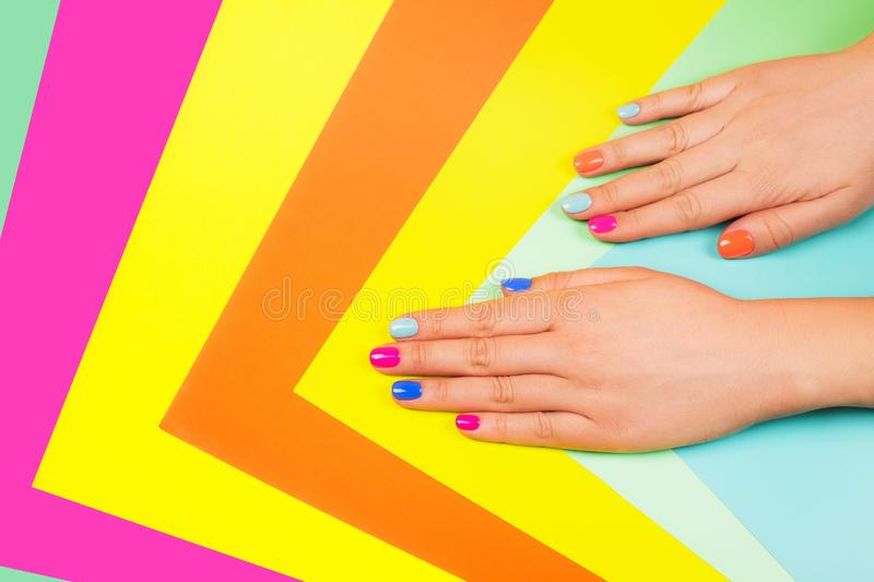 Neon manicure on multicolored bright background in trendy colors. Flat lay style stock photo