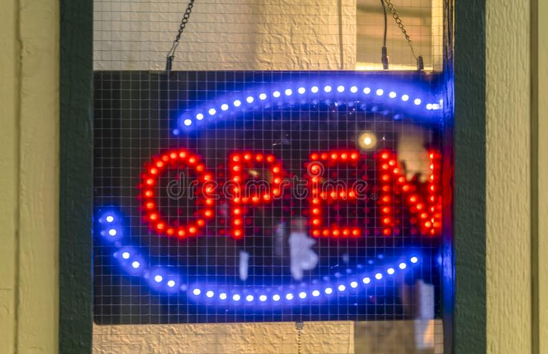 Neon Open sign on the door of an establishment. Close up of a red and blue neon Open sign hanging on the door of an establishment with screen mesh wire behind stock image