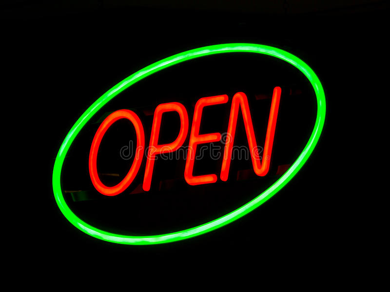 Neon Open Sign. Illuminated neon open sign outside lit up at night on a shop window to advertise that the retail outlet is serving royalty free stock photography