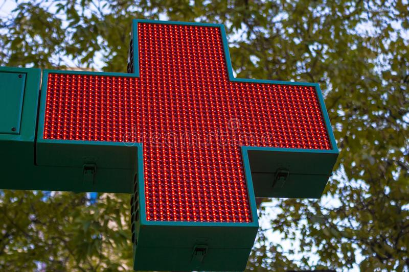 Neon red cross. A pharmacy sign, a clinic, a hospital. Sign of the red cross on the street. In the background are the leaves of trees and the sky. Autumn street royalty free stock photos