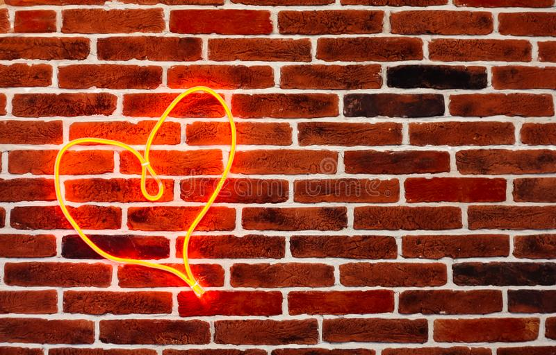 Neon red heart on the brick wall. Romantic grunge backdrop. stock photo