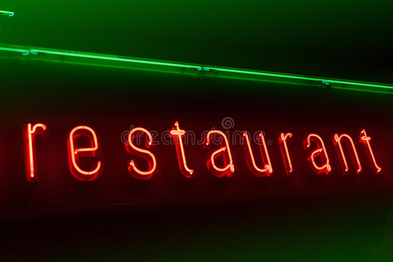 Neon restaurant signboard. Red and green neon restaurant on brown signboard royalty free stock photo