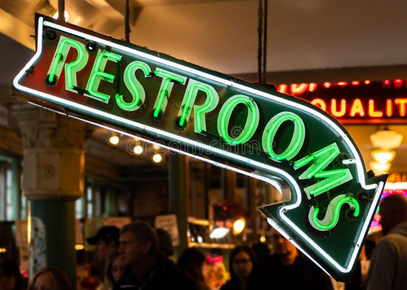 Neon Restroom Sign Pointing Down stock images