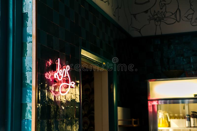 Less Neon Sign Mounted on Glass Board Near Open Window and Glass Display Rack royalty free stock photos