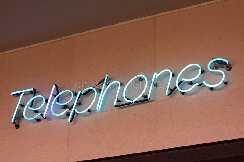 Neon sign reading Telephones. A blue neon sign outdoors reads Telephones royalty free stock photo