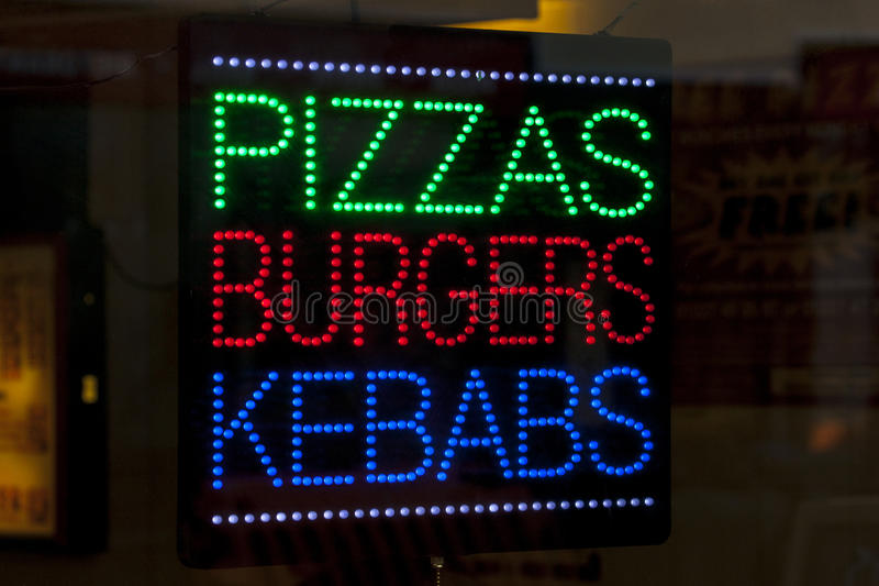 Pizzas Burgers and Kebabs. A neon sign in a takeaway shop window advertising Pizzas, Burgers, and Kebabs stock photography