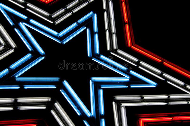 Neon Star. Large neon lit star with patriotic colors of red, white and blue. Shot against the night sky stock photos