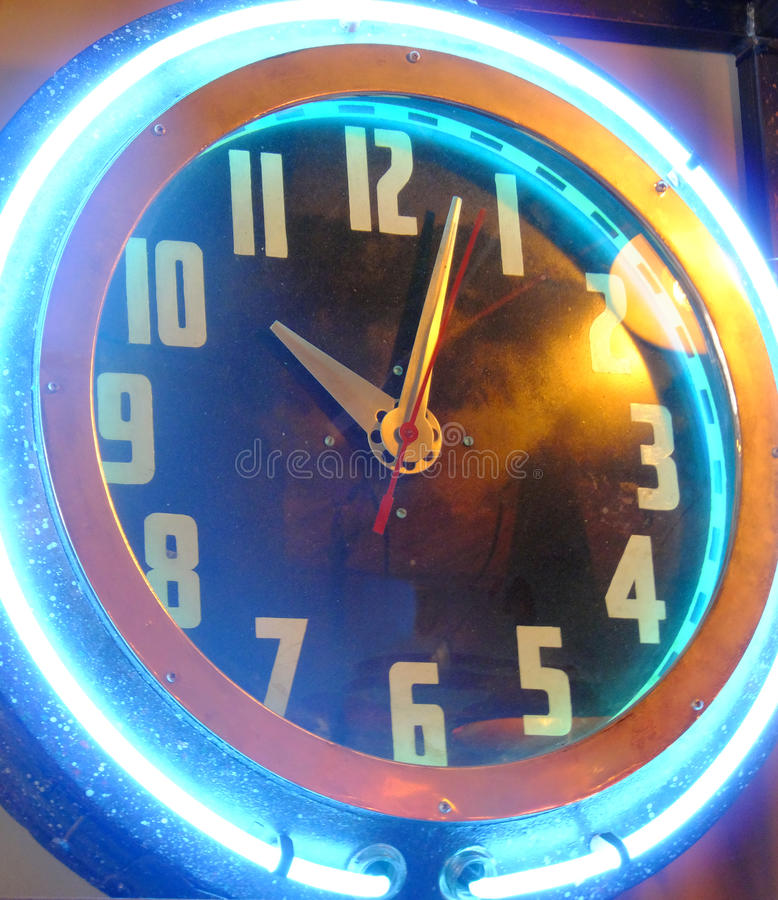 Neon Ticker. Art deco style analog antique clock with neon gas tube framing clock face stock images