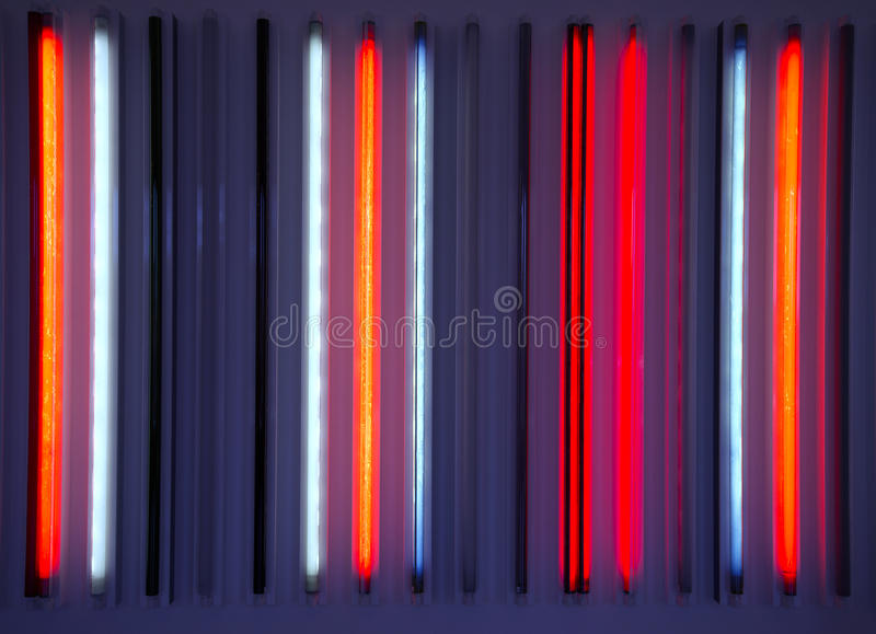 Neon tubes. In vertical glowing colors and tones of red, blue and purple stock photography