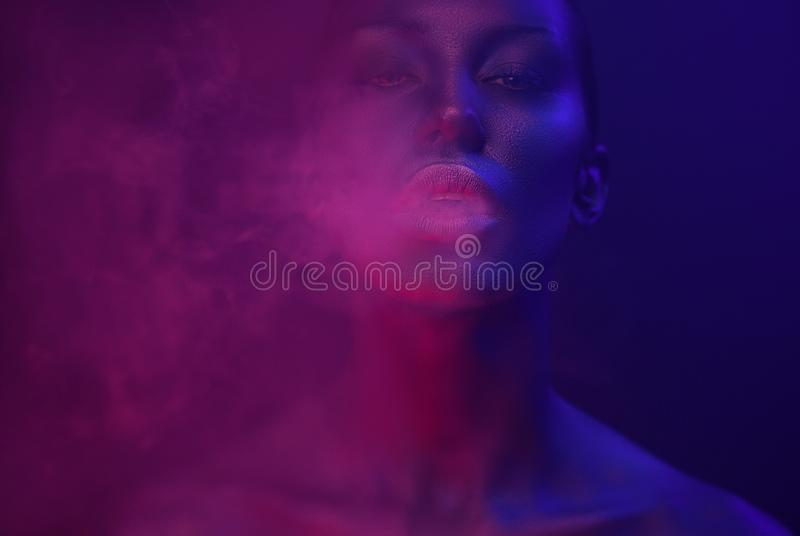 Neon Vape Party, Nightlife. Beautiful Woman with glamorous makeup vaping in Nightclub neon, exhaling smoke. Girl smoking. Vaporizer in Club. Blue mystic smoke royalty free stock images