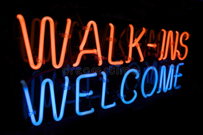 Neon Walk In's Welcome sign. Red and Green WALK INS WELCOME Sign lights up the night stock photo