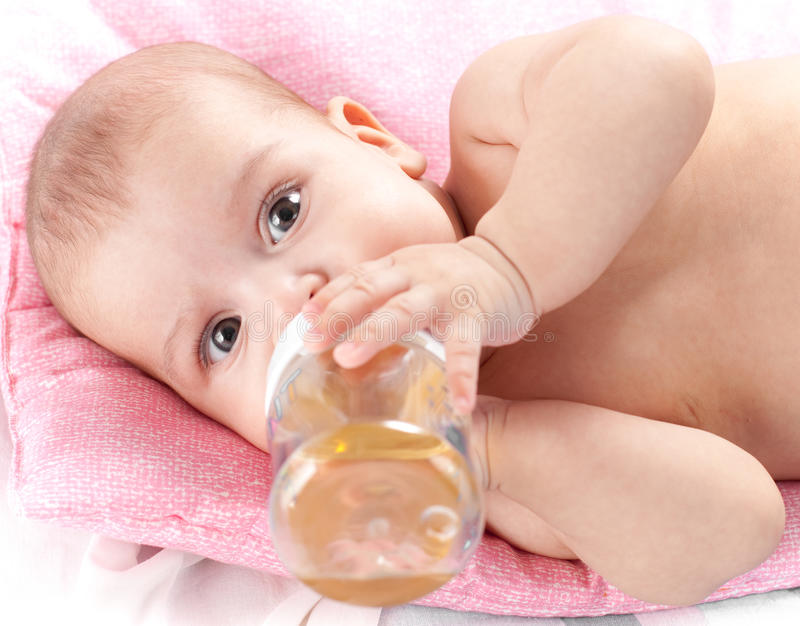 Neonata adorabile che beve dalla bottiglia fotografie stock libere da diritti