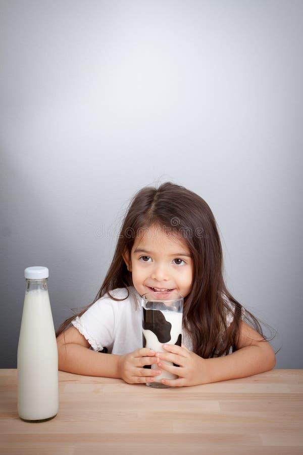 Neonata adorabile che tiene bicchiere di latte e latte alimentare fotografia stock libera da diritti