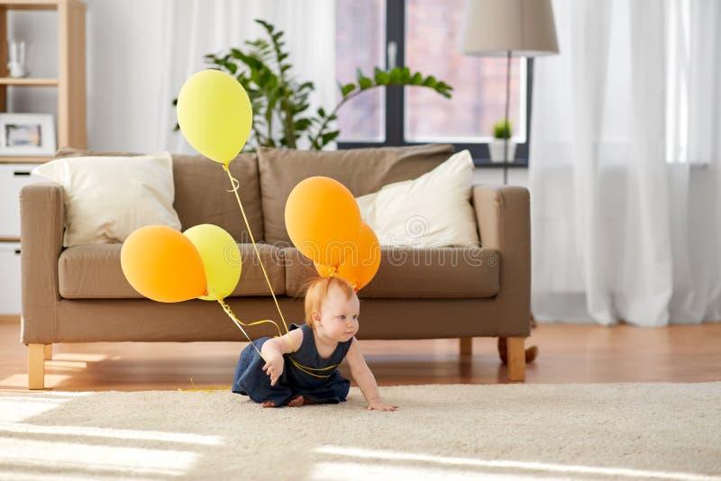 Neonata adorabile della testarossa con i palloni a casa fotografia stock libera da diritti