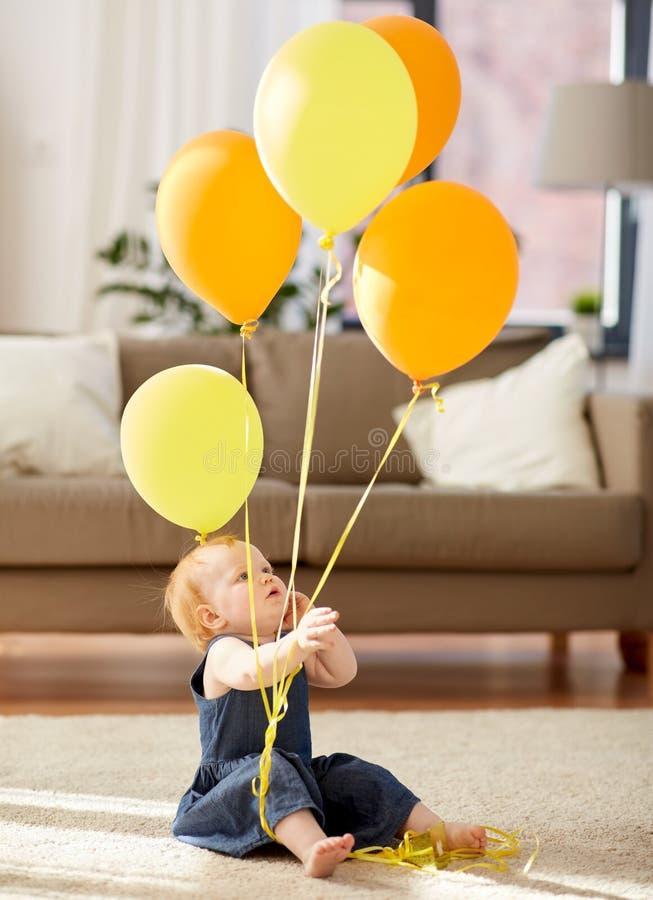 Neonata adorabile della testarossa con i palloni a casa immagine stock libera da diritti