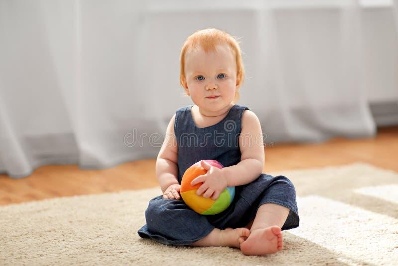 Neonata adorabile della testarossa con la palla del giocattolo a casa immagine stock