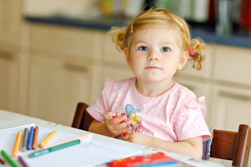 Neonata adorabile sveglia che impara pittura con le matite Piccolo bambino del bambino che disegna a casa, facendo uso della penn immagini stock libere da diritti