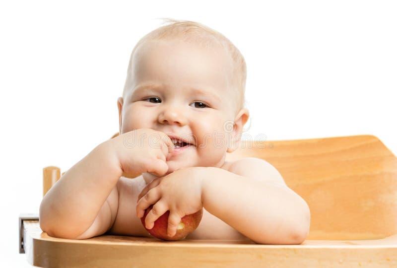 Neonata allegra che mangia mela mentre sedendosi nel seggiolone fotografie stock