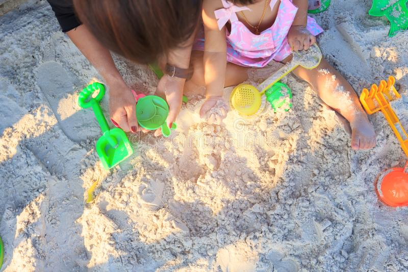 Neonata asiatica e genitore svegli che giocano spiaggia di sabbia fotografia stock libera da diritti