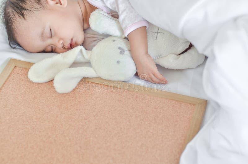 Neonata asiatica sveglia che dorme sul letto con un coniglietto del giocattolo e una b immagine stock