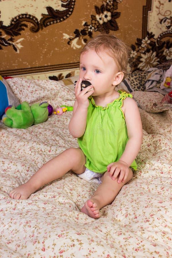 Neonata bionda sveglia con i bei occhi azzurri che si siedono e che sorridono con il giocattolo fotografia stock libera da diritti