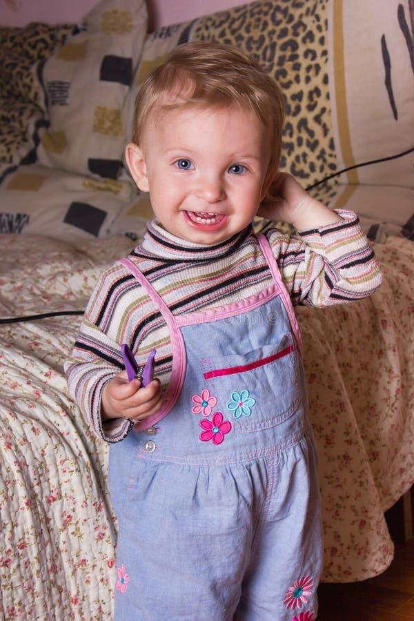 Neonata bionda sveglia con i bei occhi azzurri che si siedono e che sorridono con il giocattolo immagine stock libera da diritti