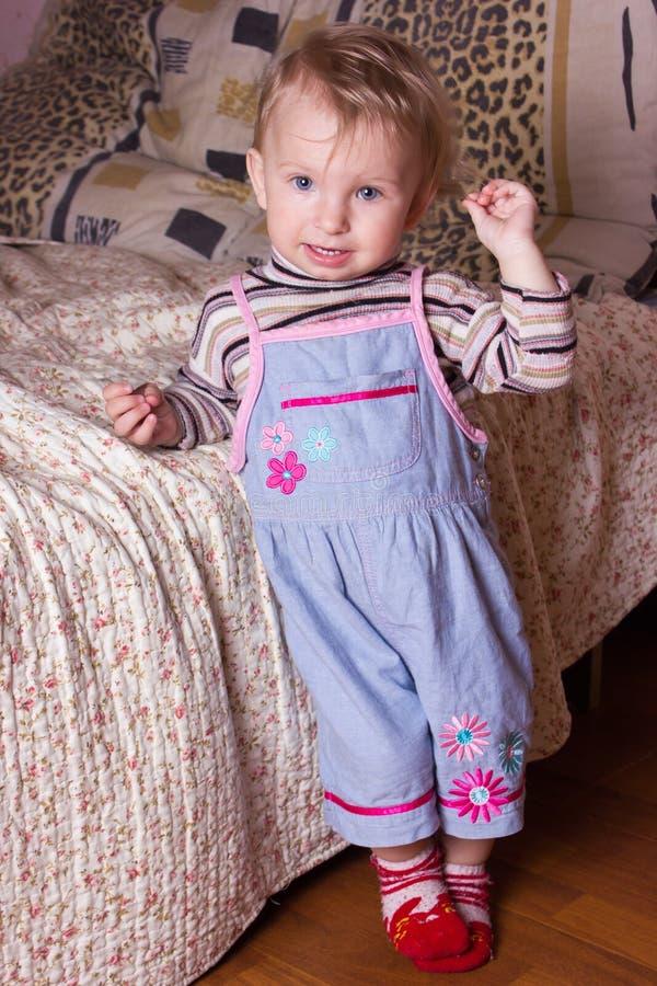 Neonata bionda sveglia con i bei occhi azzurri che si siedono e che sorridono con il giocattolo immagini stock libere da diritti