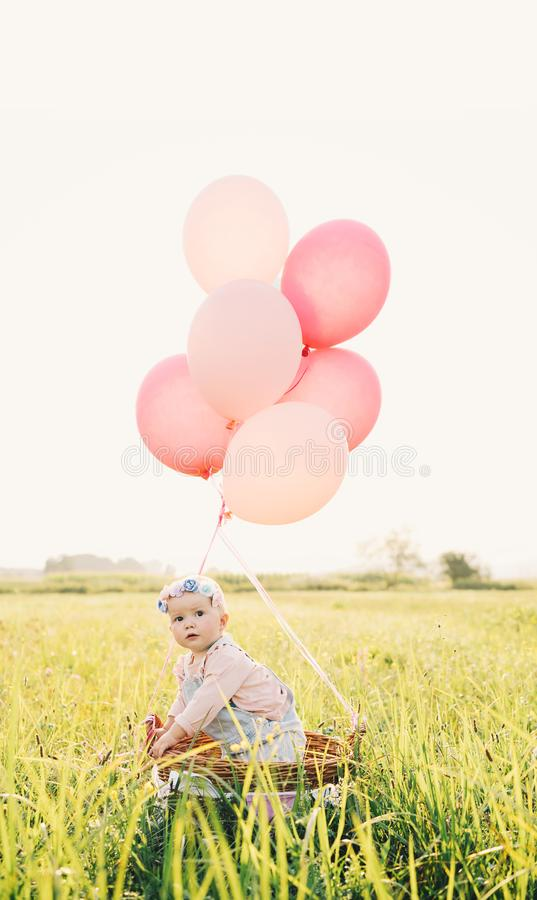 Neonata in canestro di vimini con i palloni sulla natura ad estate fotografia stock