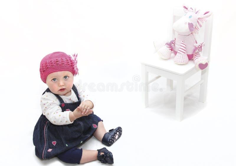 Neonata in cappello e giocattolo dentellare fotografia stock