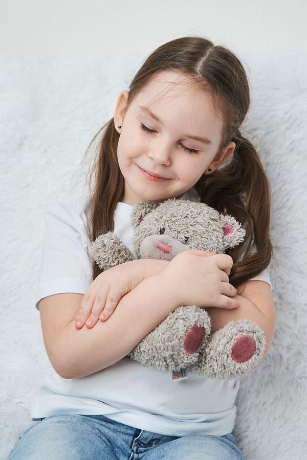 Neonata che abbraccia l'orso della peluche, sedentesi su un sofà bianco Fine in su immagini stock libere da diritti