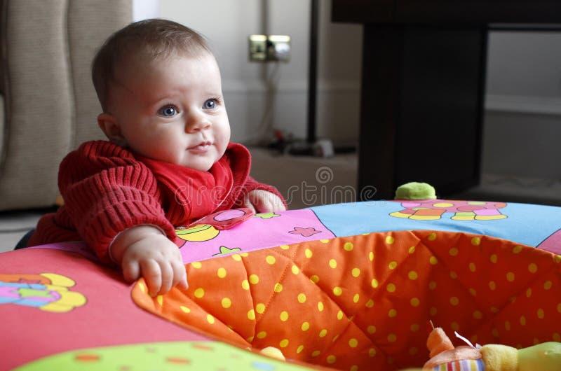 Neonata che gioca con il giocattolo (playpen) fotografia stock