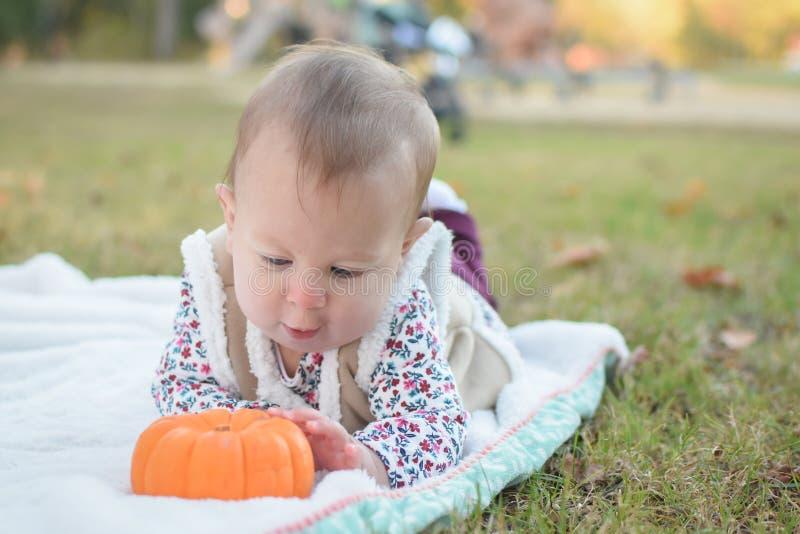 Neonata che gioca con una zucca fotografia stock