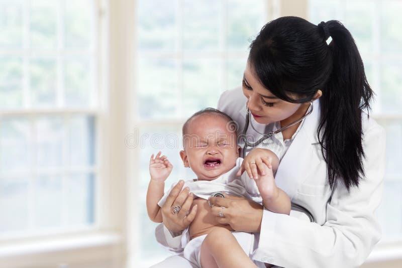 Neonata che grida una volta esaminato da medico fotografia stock libera da diritti