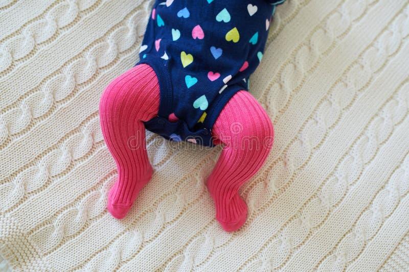 Neonata che indossa le calzamaglia rosa e onesie variopinto fotografia stock
