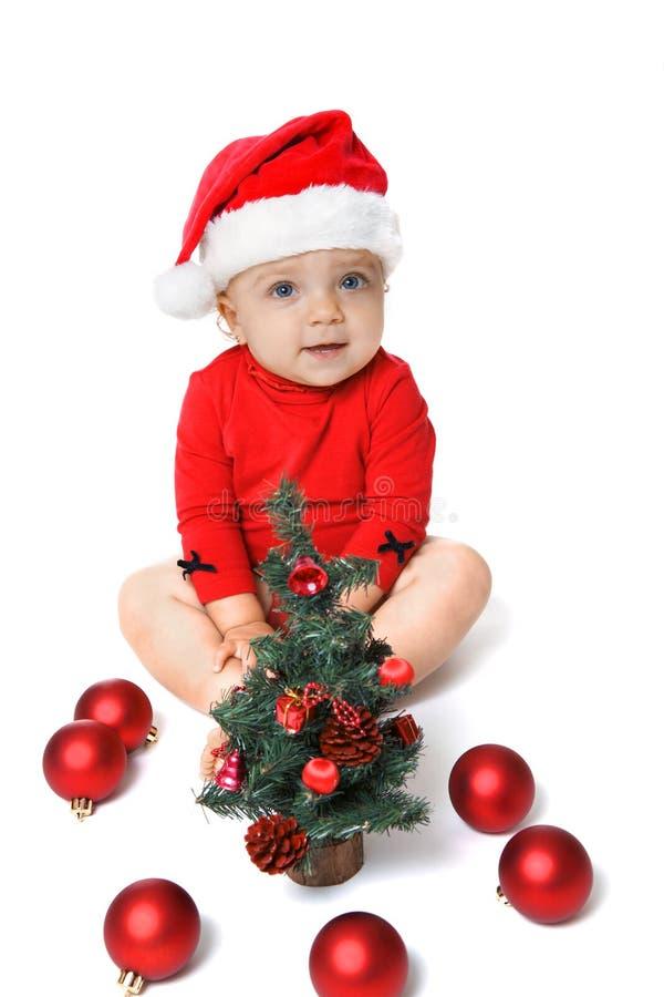 Neonata che indossa un cappello di Santa Claus e un albero di Natale immagine stock libera da diritti